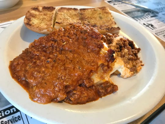 Dino's lasagna is a specialty of the house bathed in a mouthwatering hearty tomato sauce.