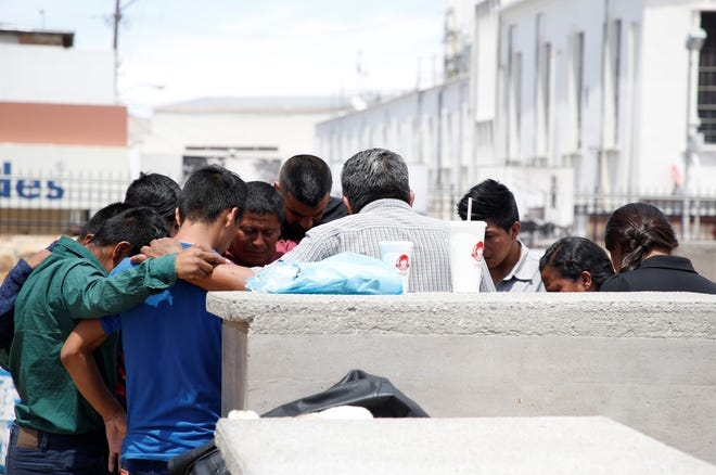 A group of migrants returned to Juárez, under the Trump administration's Migrant Protection Protocols, pray outside the Catedral de Nuestra Senora de Guadalupe.