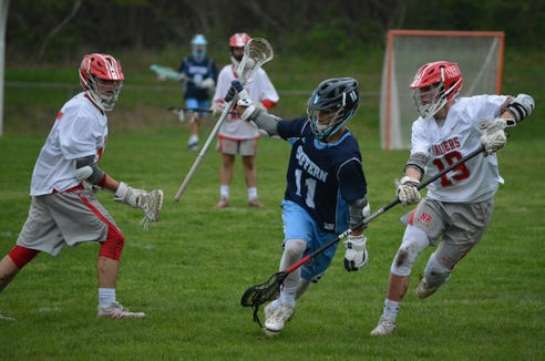 Suffern attackman Tim Fay attempts to elude Luke Morris during a 9-3 loss to North Rockland on May 3, 2018.