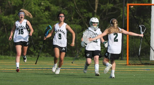 Archmere's Maura Smeader (22) moves to share a hug with Kate Olsen as the Auks hold off an Ursuline rally to win, 15-14, at Archmere Academy Friday.