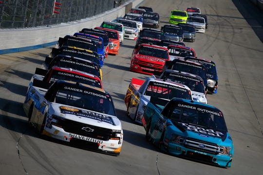 DOVER, DE - MAY 03:  (L)  Sheldon Creed, driver of the #2 Chevrolet Accessories Chevrolet, and (R) Johnny Sauter, driver of the #13 Tenda Heal Ford, lead a pack of cars during the NASCAR Gander Outdoors Truck Series JEGS 200 at Dover International Speedway on May 3, 2019 in Dover, Delaware.