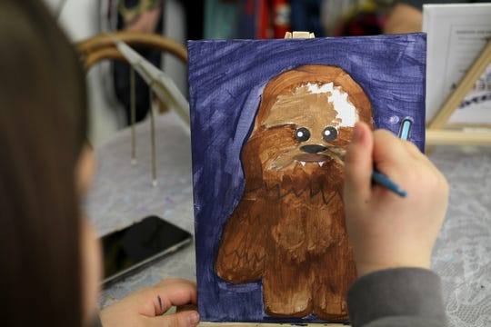 Kelcie Watson paints Chewbacca Saturday, May 4, 2019, at Pat's Tea Shoppe's first Star Wars Day Party.
