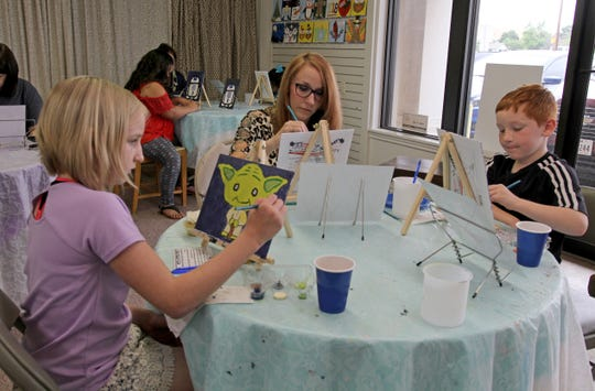Abigail, left, Kendra and Evan Childers paint different characters Saturday, May 4, 2019, at Pat's Tea Shoppe's first Star Wars Day Party.