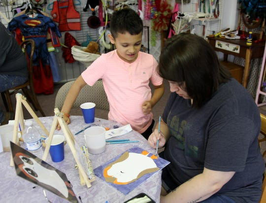 Jayce Montes watches as Liz Chavez paints a porg Saturday, May 4, 2019, at Pat's Tea Shoppe's first Star Wars Day Party.