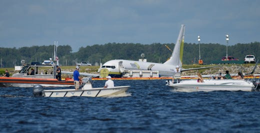 A charter plane carrying 143 people and traveling from Cuba to north Florida sits in a river at the end of a runway, Saturday, May 4, 2019 in Jacksonville, Fla.  The Boeing 737 arriving at Naval Air Station Jacksonville from Naval Station Guantanamo Bay, Cuba, with 136 passengers and seven aircrew slid off the runway Friday night into the St. Johns River, a NAS Jacksonville news release said.