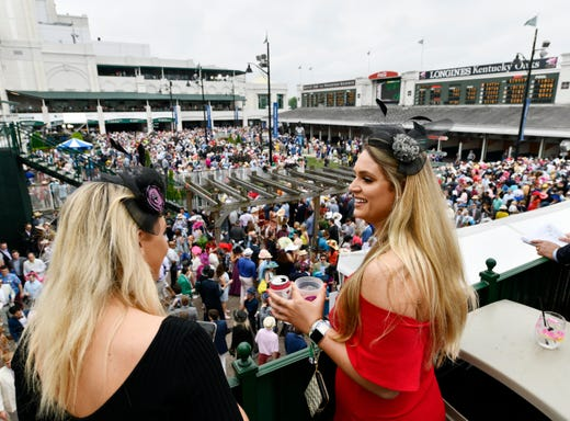 Women in derby attire look out towards the paddock area at Churchill Downs ahead of the 145th running of the Kentucky Derby.