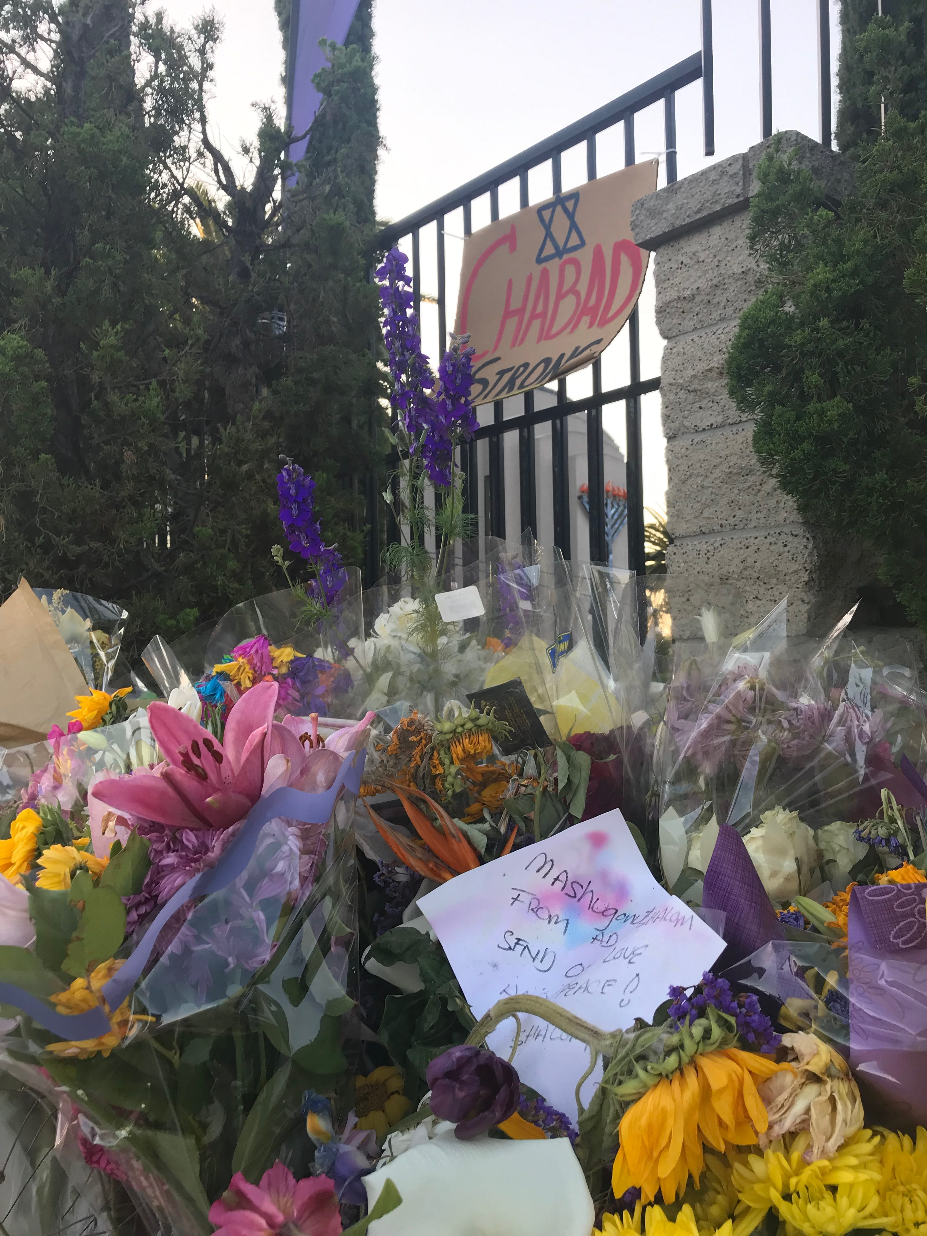 Flowers and messages of support line a street corner adjacent to Chabad of Poway on Friday night.
