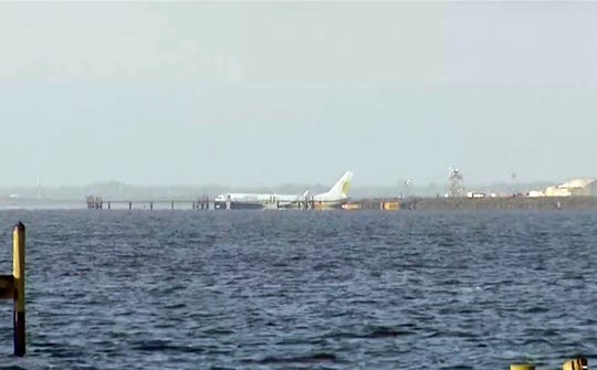 A charter plane carrying 143 people and traveling from Cuba to north Florida sits in a river at the end of a runway, Saturday, May 4, 2019 in Jacksonville, Fla.    The Boeing 737 arriving at Naval Air Station Jacksonville from Naval Station Guantanamo Bay, Cuba, with 136 passengers and seven aircrew slid off the runway Friday night into the St. Johns River, a NAS Jacksonville news release said. (AP Photo/APTN) ORG XMIT: NY107