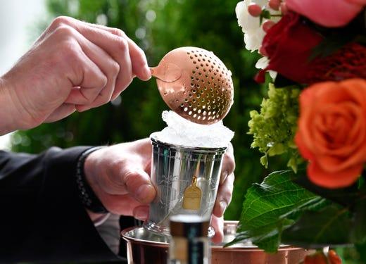 A bartender prepares a thousand dollar mint julep.