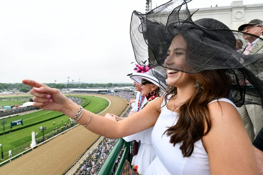 Lauren Wilt and other fans cheers during a pre-derby race at Churchill Downs.