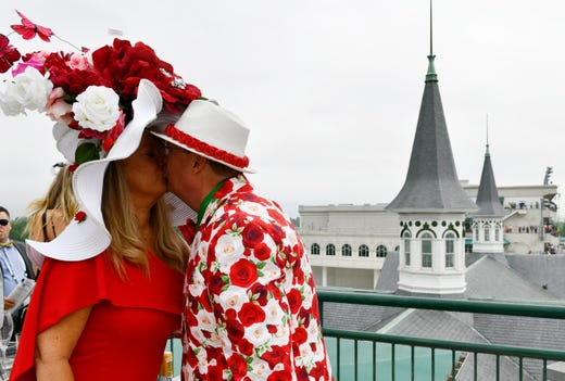 A couple in derby attire kiss with the Churchill Downs twin spires in the background.