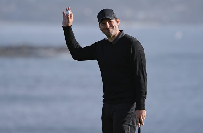 Tony Romo acknowledges the crowd on the 18th green during the third round of the AT&T Pebble Beach Pro-Am golf tournament.