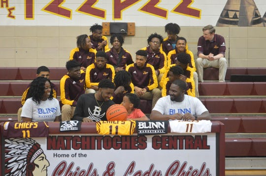 Natchitoches Central's CJ Carpenter (second left) smiles after signing with Blinn College Friday.