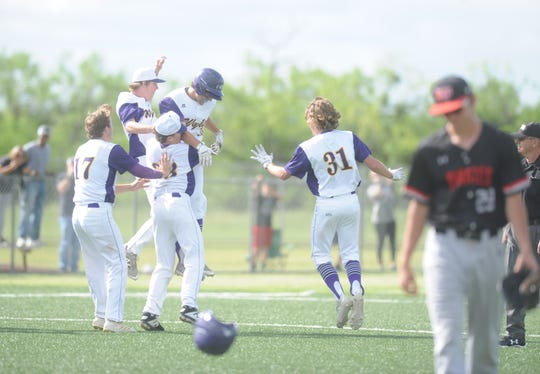 Wylie teammates congratulate Jaxon Hansen following his game-winning hit in Game 3 of a Region I-5A bi-district series against Lubbock-Cooper on Saturday, May 4, 2019, at Bulldog Field in Abilene.