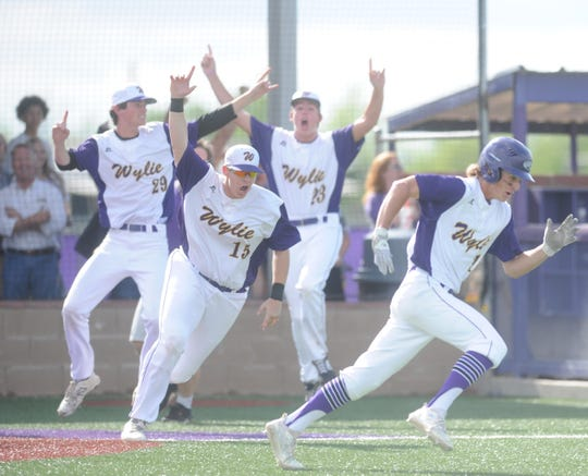 Wylie's Walker Piland (29), Hunter Fulkerson (15) and Cade Weaver (23) celebrate as Tyler Martin races to congratulate Jaxon Hansen after the game-winning hit of Game 3 of a Region I-5A bi-district series against Lubbock-Cooper on Saturday, May 4, 2019, at Bulldog Field in Abilene.
