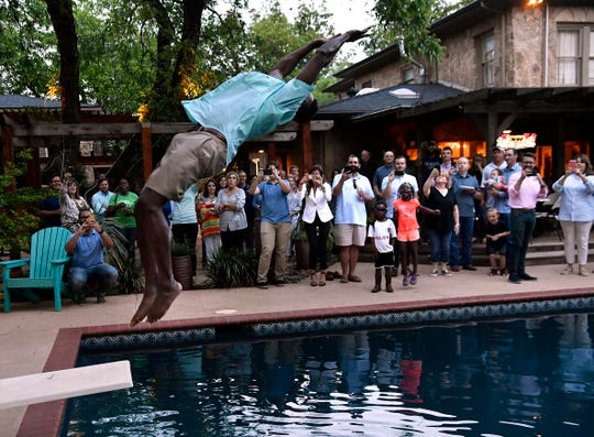 Abilene City Council candidate Travis Craver celebrates his win in Saturday's election by performing a backflip off a swimming pool diving board.