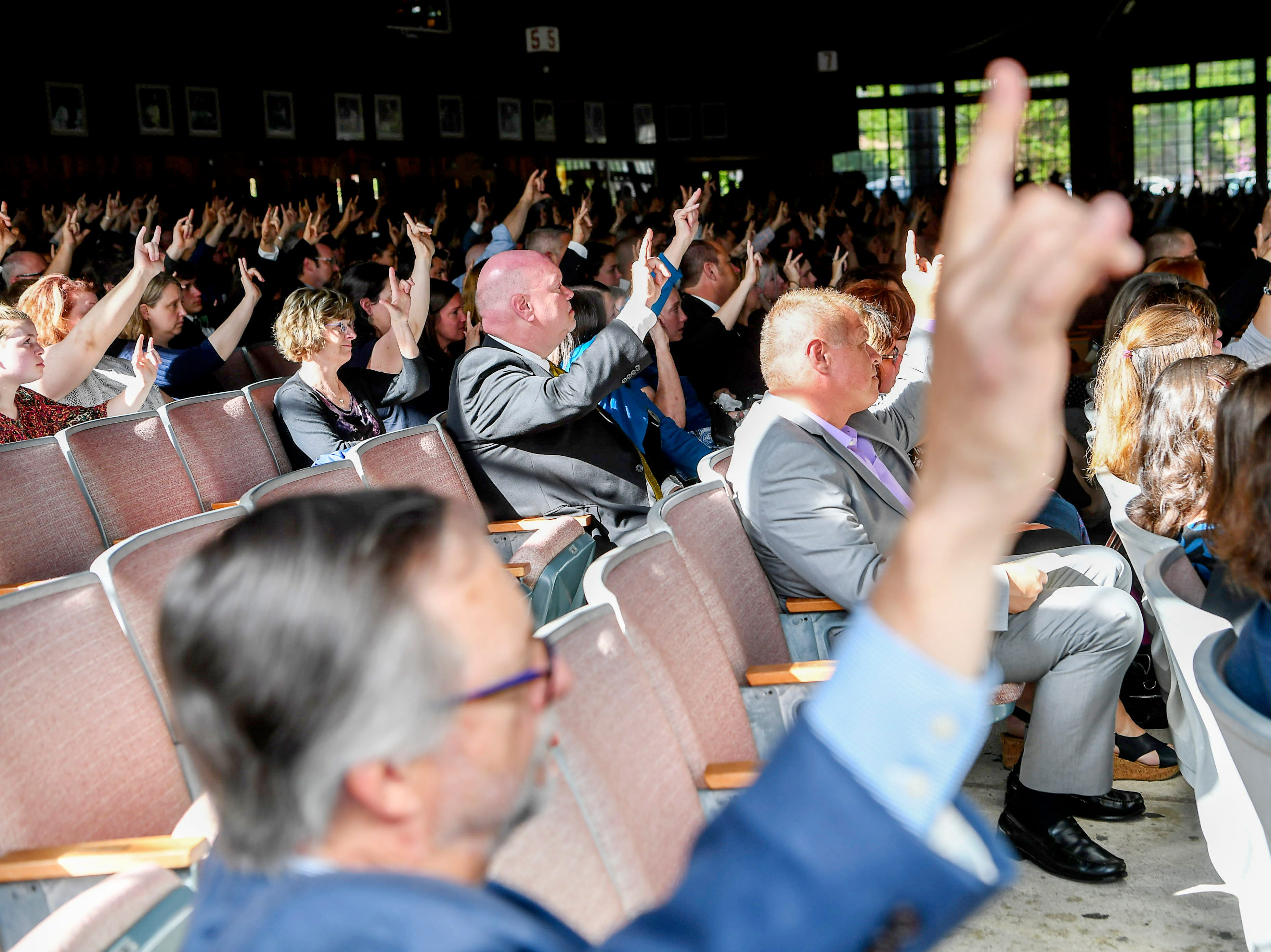 "Mourners raise their hands, signing ""I love you,"" during Riley Howell funeral May 5, 2019."
