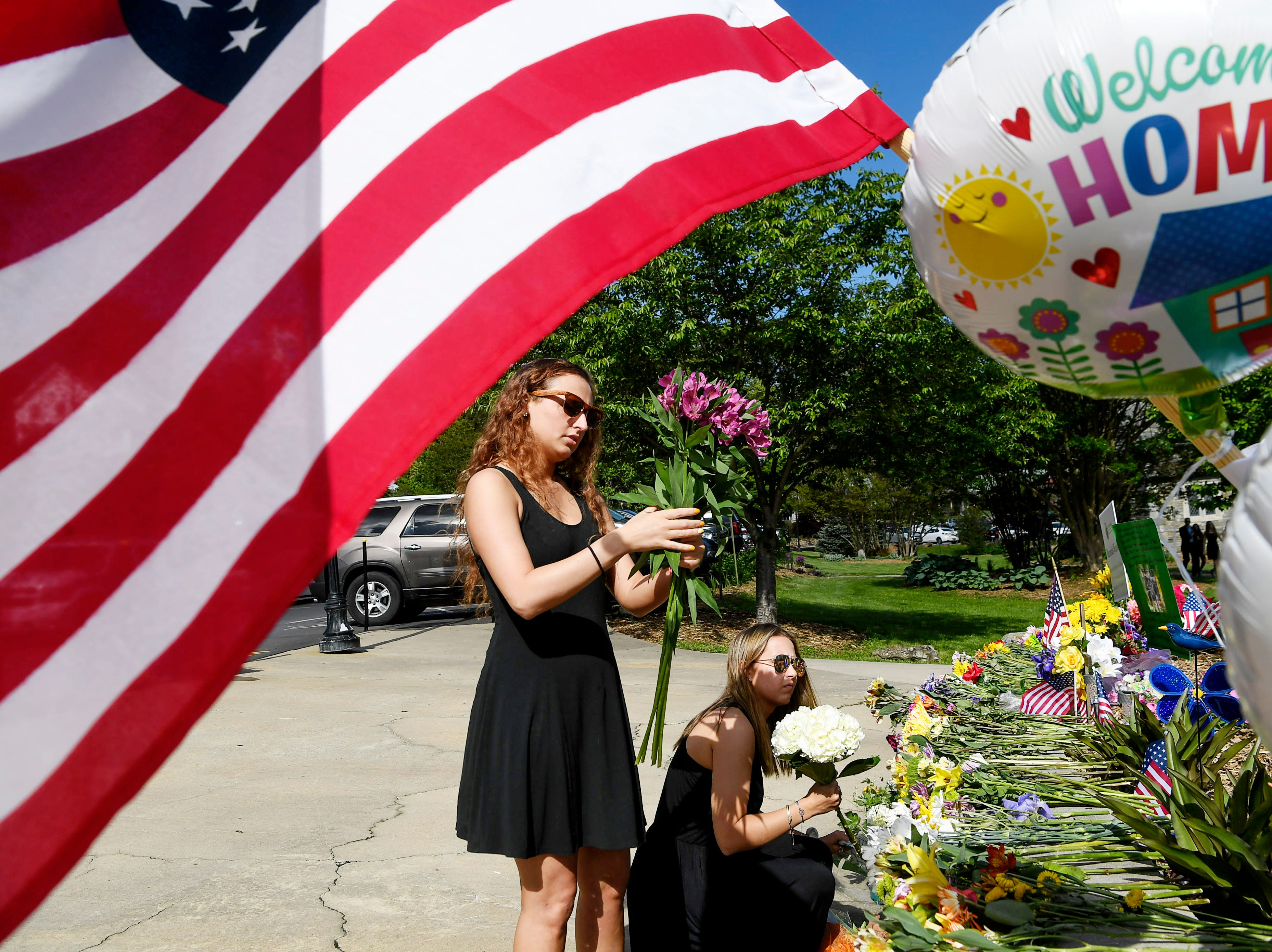 Brittney Jones, 22, left, and Kenzie Johnson, 20, place flowers near Stuart Auditorium in Lake Junaluska before the funeral of Riley Howell, May 5, 2019.