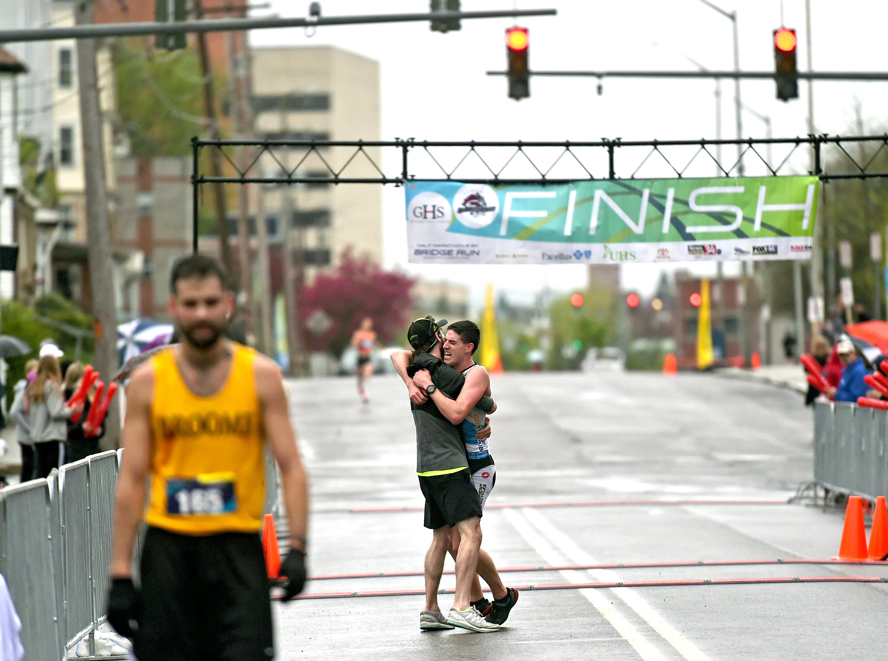 Ryan Brizzolara of Maine is greeted at the finishing line of the half marathon during the Greater Binghamton Bridge Run Half Marathon and 5K, Sunday, May 5, 2019.