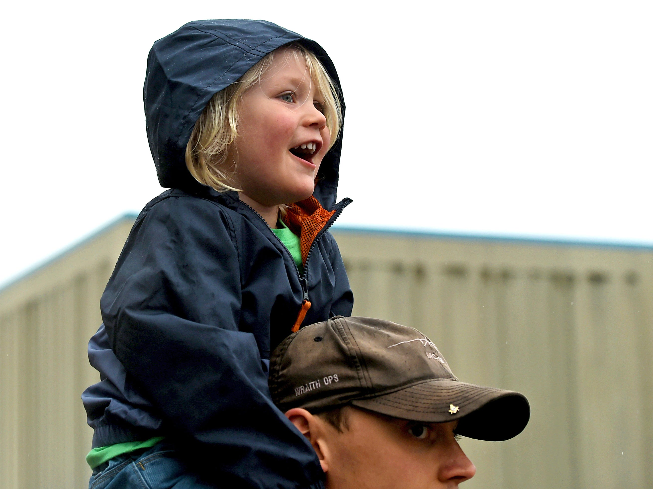 Liam Murphy, age 3, of Watertown, sits on top of his father, Brandon Murphy, as he cheers on his mom Amanda Murphy at the start of Greater Binghamton Bridge Run Half Marathon on Sunday, May 5, 2019.