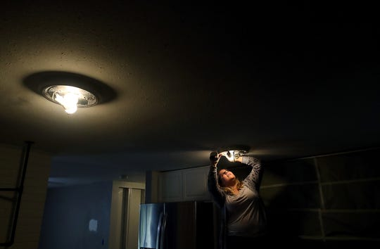 Katie Barnes affixes painters tape around a light fixture in the kitchen of her Port Orchard home on Thursday, May 2, 2019. Katie and her husband Ryan and son were forced to leave the home when tests showed that it was contaminated by methamphetamine.