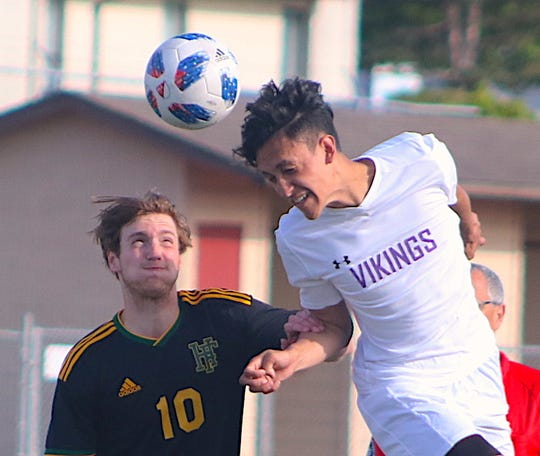 North Kitsap soccer player Joey Gore heads the ball upfield during the Vikings' Class 2A West Central District playoff game Saturday against Foss.