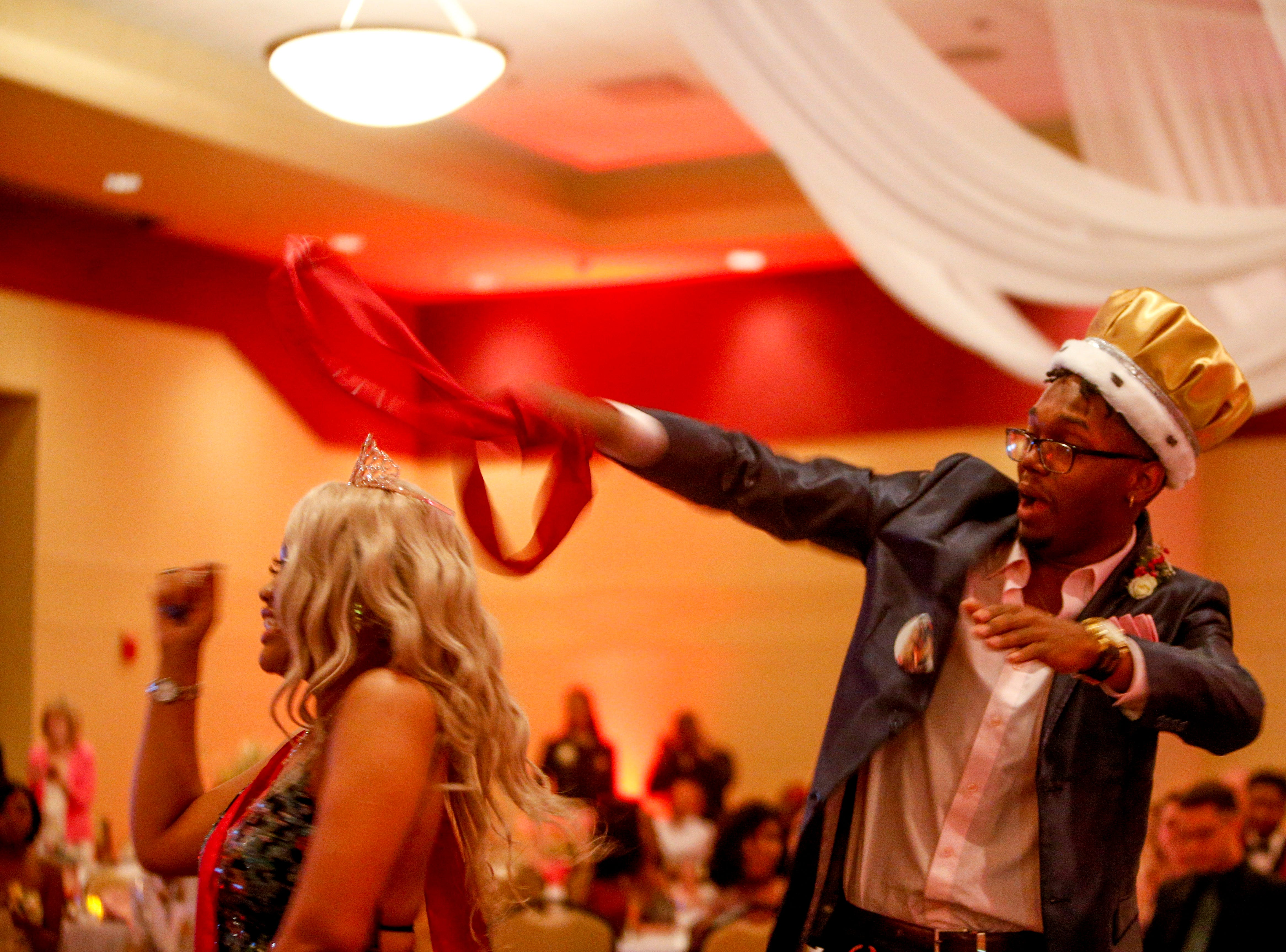 """Prom king Kaos Armstrong, right, uses his sash as a mock lasso while dancing with prom queen Adannis Delis-Luna, left, as hundreds of students from Kenwood High School celebrated their 2019 prom themed """"Cherish the Moment"""" at Valor Hall in Oak Grove, KY., on Saturday, May 4, 2019."""