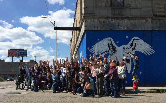A crowd poses for a photo outside the Grande Ballroom during an informal gathering to celebrate the late Russ Gibb on Sunday, May 5, 2019, in Detroit.