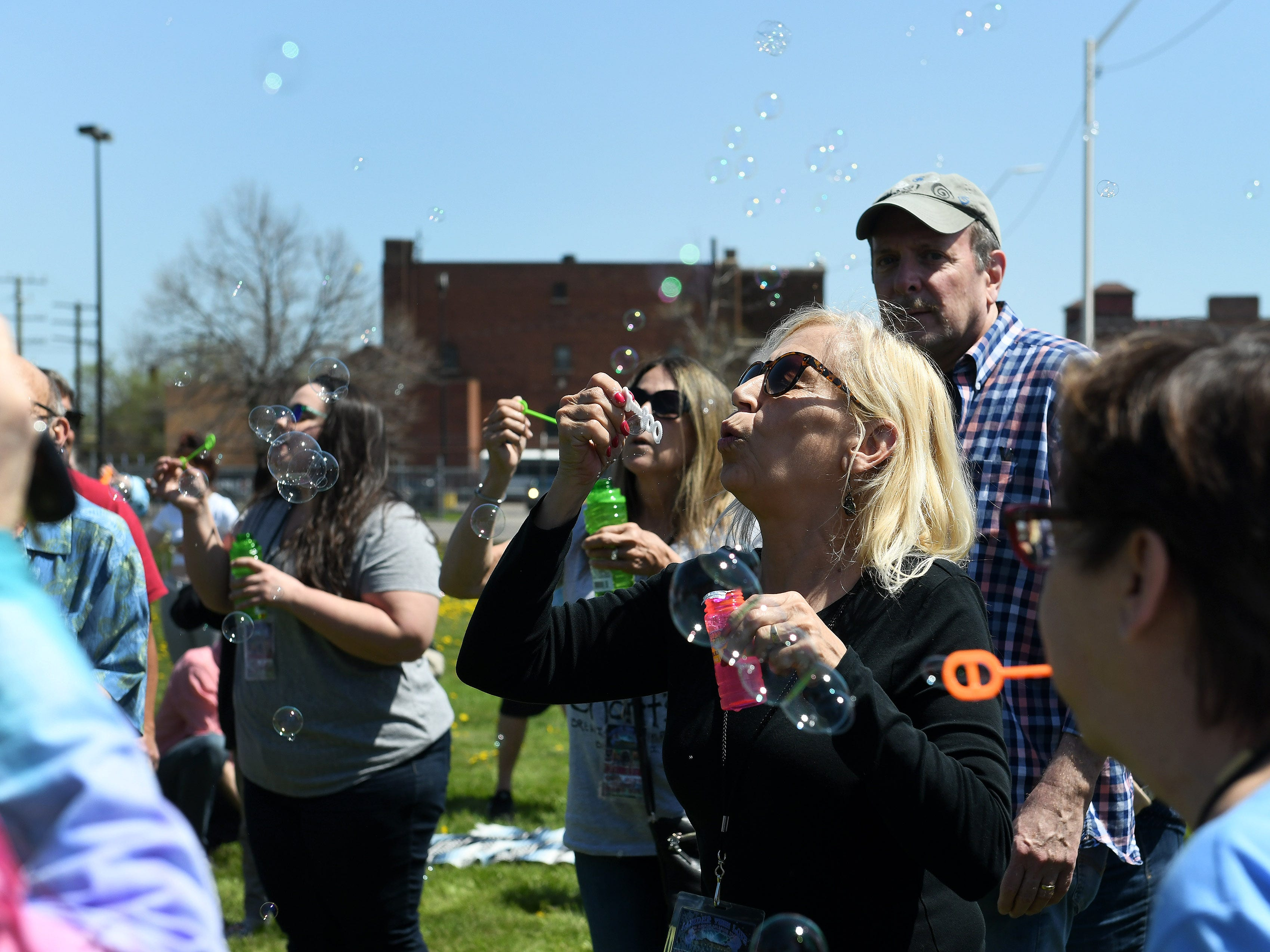 Linda Flynn, 62, of Taylor, blond with sunglasses, blows bubbles with others as people gather to celebrate the life of Russ Gibb.