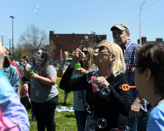 Linda Flynn, 62, of Taylo, right, in sunglasses, blows bubbles as friends and supporters gather to celebrate the life of Russ Gibb.