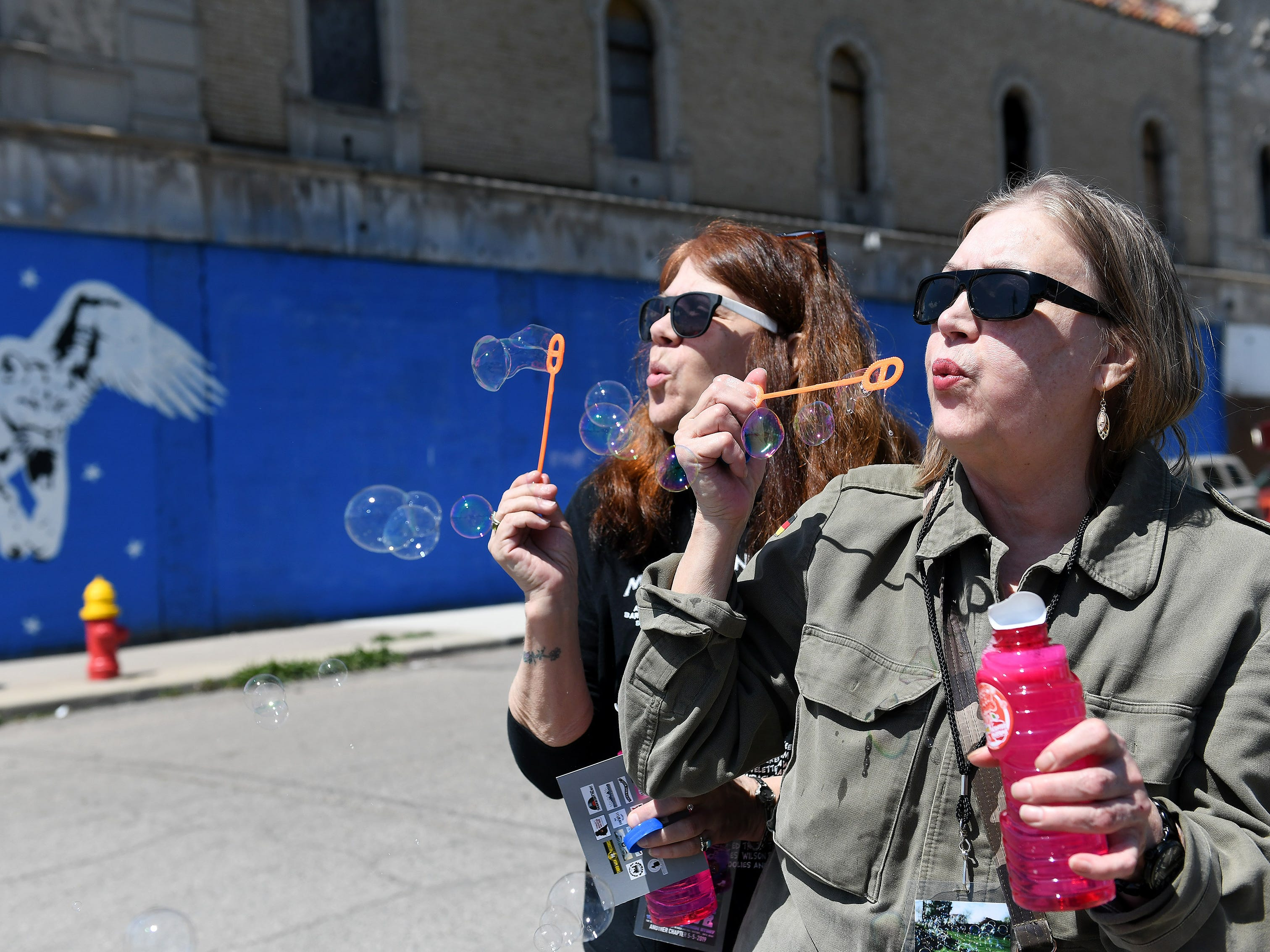 From left, Sheryl Gatt and Terry Seisser both of Novi blow bubbles as people gather to celebrate the life of Russ Gibb outside the Grande Ballroom on Grand River Boulevard.