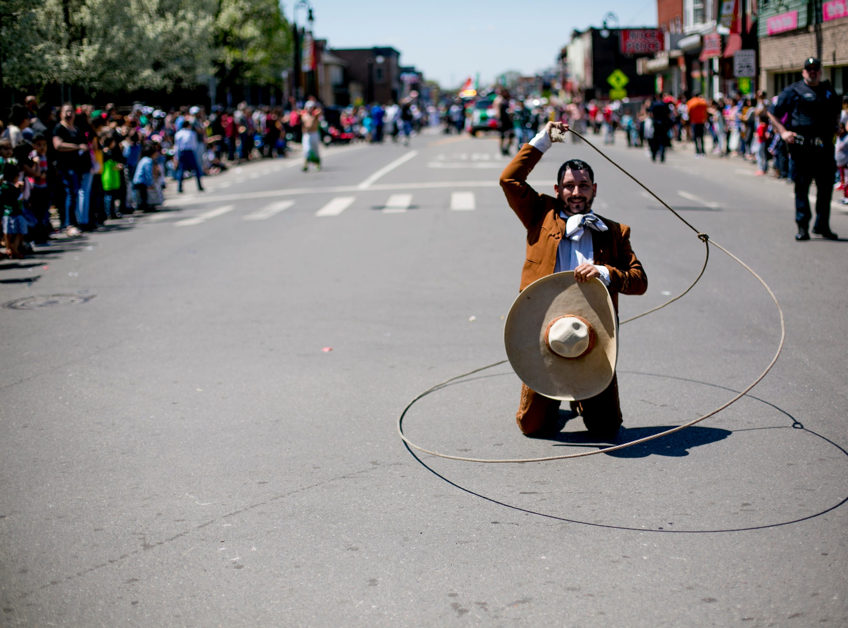 A man twirls a lasso as he walks in the 55th Annual Cinco de Mayo parade along Vernor Highway in southwest Detroit.
