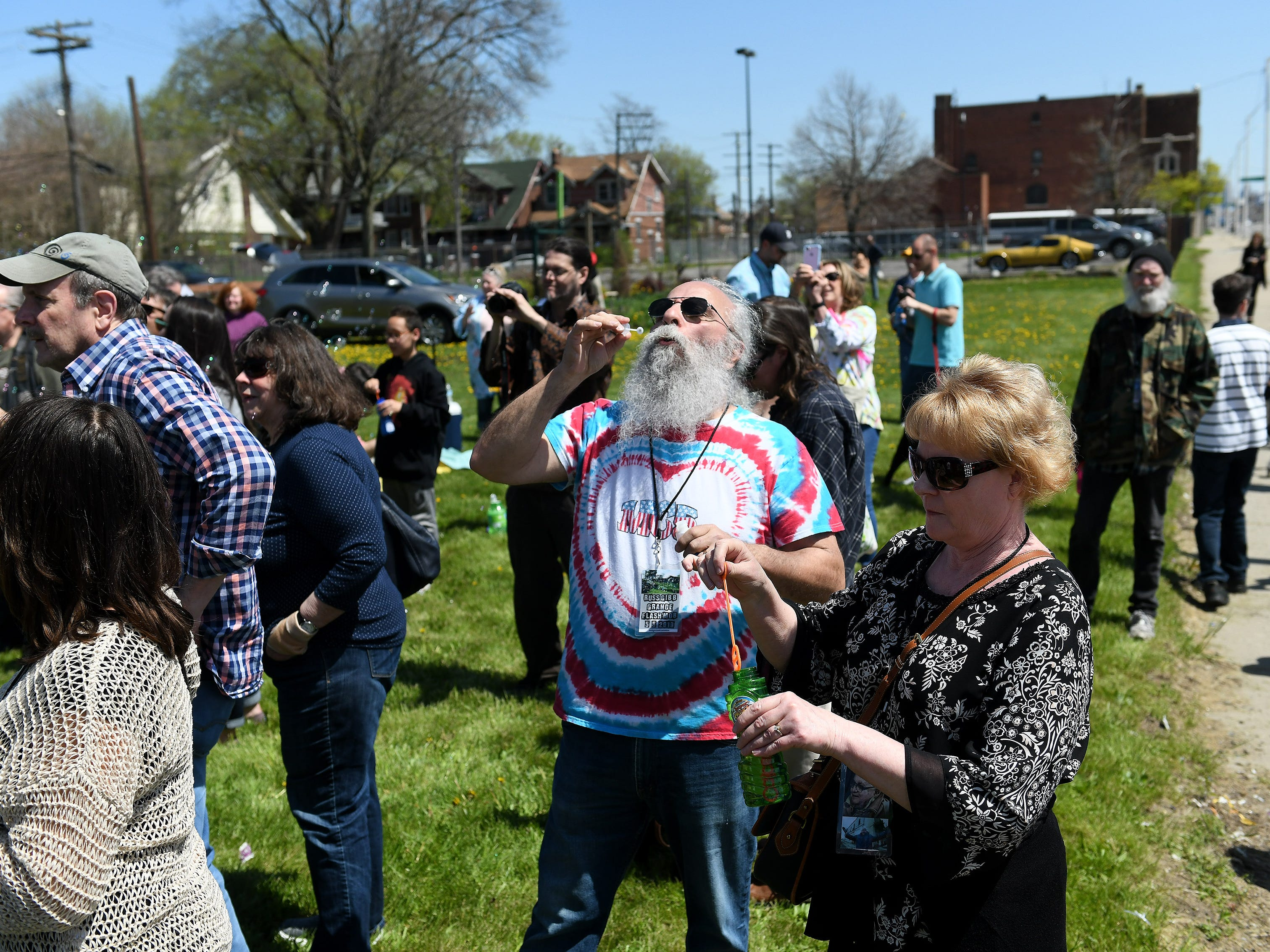 Joe and Kelly Cusumano of Warren blow bubbles as people gather to celebrate the life of Russ Gibb outside the Grande Ballroom.