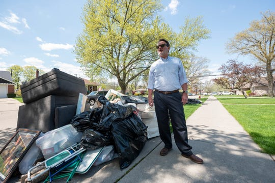U.S. Senator Gary Peters finds piles of furniture and other household items at the curb of a home on Luana Avenue in Allen Park during a tour of flood-damaged areas in Metro Detroit on Sunday.