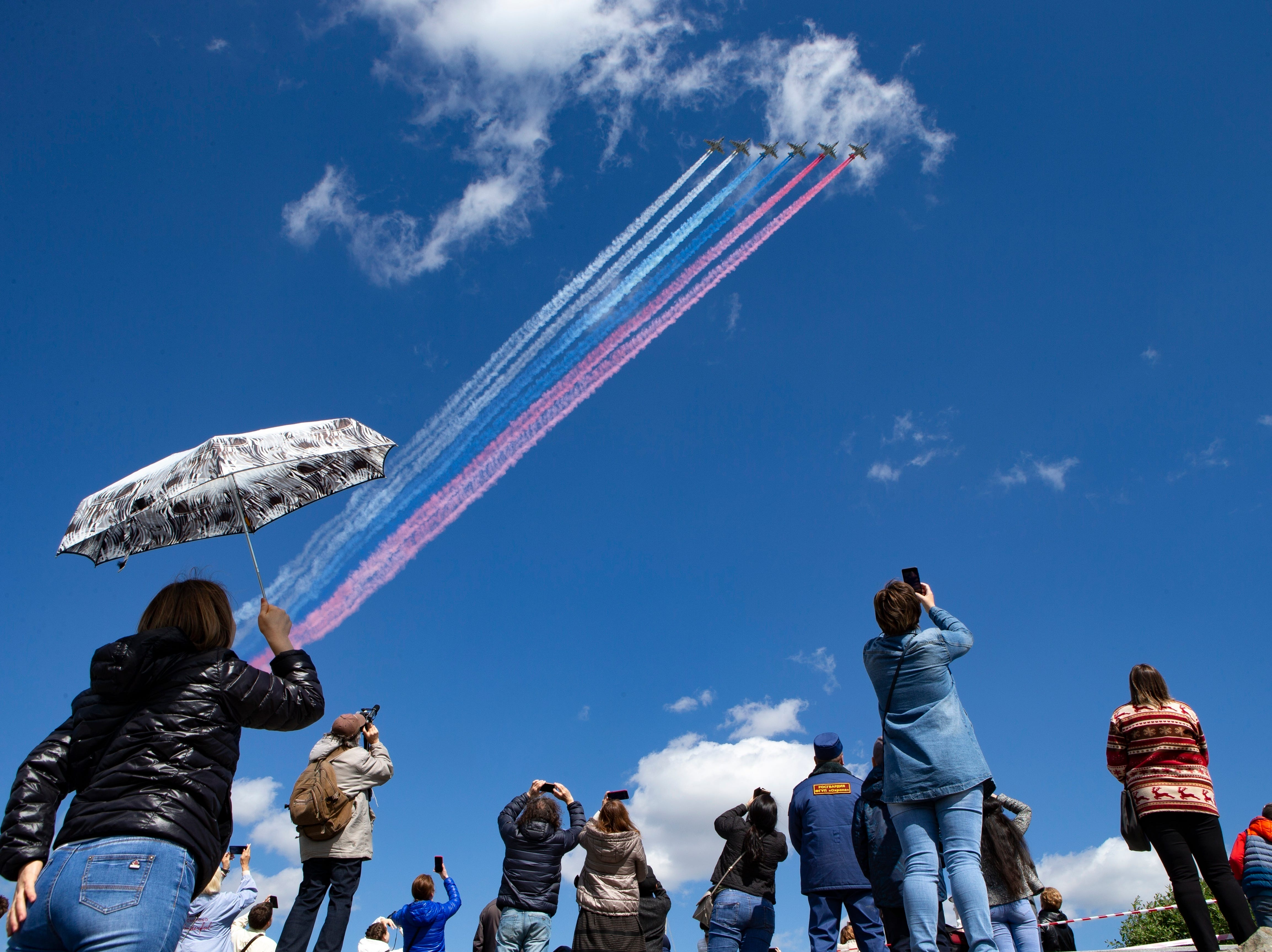 Tourists watch and photograph Russian Air Force jets flying over Red Square during a rehearsal for the Victory Day military parade in Moscow, Russia, on Saturday, May, 4, 2019. The parade will take place at Moscow's Red Square on May 9 to celebrate 74 years of the victory in WWII.