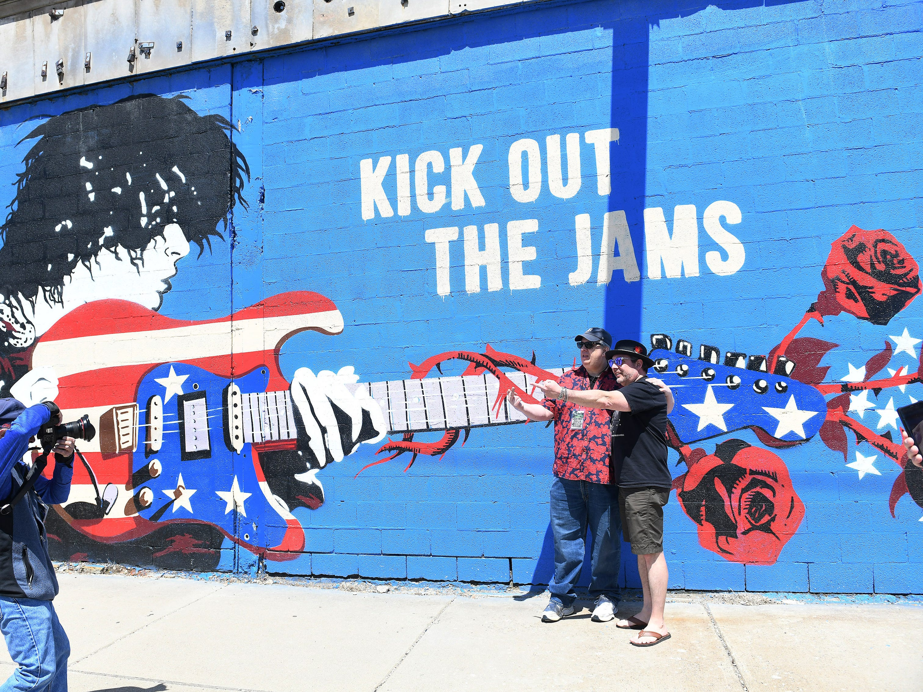 Leo Early from Friends of the Grande, left, and filmmaker Tony D'Annunzio are photographed in front of the mural on the front of the Grande Ballroom as people gather to celebrate the life of Russ Gibb in Detroit on May 5, 2019.   Memorial service details are still to come.