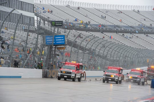 Track drying teams work to dry the track at Dover International Speedway on Sunday.