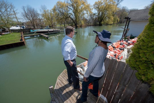 U.S. Sen. Gary Peters, left, is given a tour May 5 of flood-damaged areas around the canal that separates Harbor Island and Klenk Island by Judge Deborah Thomas who lives on the canal, in Detroit. The persistent issues are prompting officials to require sandbags at city sites.