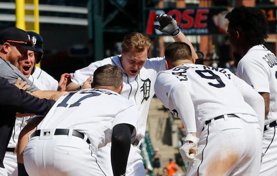 Brandon Dixon is greeted at home plate after his three-run home run in the 10th inning lifted the Tigers to a 5-2 victory over the Royals on Sunday at Comerica Park.