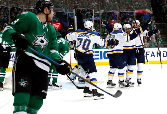 St. Louis' David Perron, second from right, is congratulated by teammates after scoring as Dallas' Esa Lindell watches during the second period of Game 6 on Sunday.