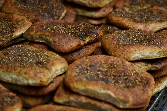 Loaves of Middle Eastern bread, dusted with zaatar, sit cooling hot from the oven as some 20 volunteers bake 3,000 pieces and over 1,800 cookies for the start of Ramadan, the Muslim holy month, at the Islamic Center of America in Dearborn, Michigan on May 5, 2019.