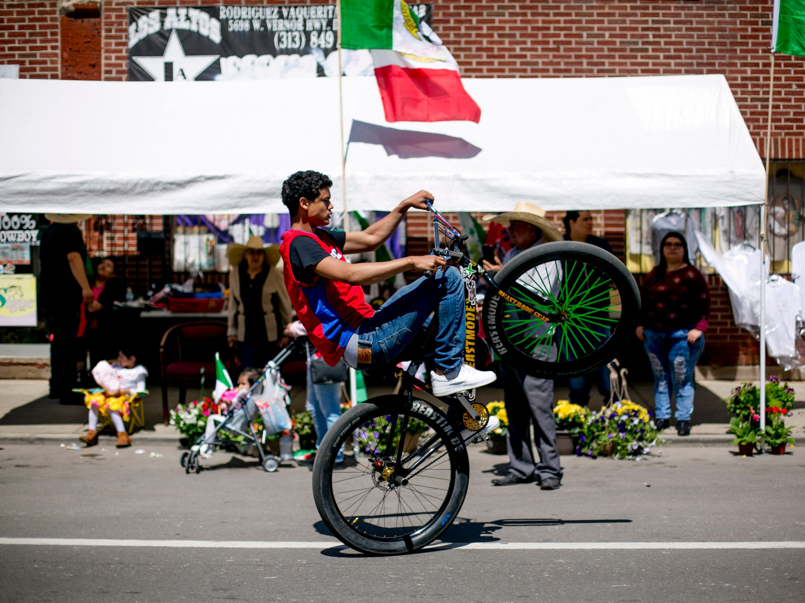 A man rides a bike in the 55th Annual Cinco de Mayo parade along Vernor Highway.