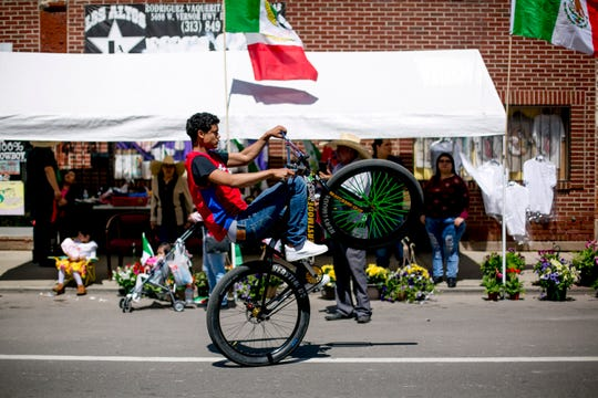 A man rides a bike in the 55th Annual Cinco de Mayo parade.