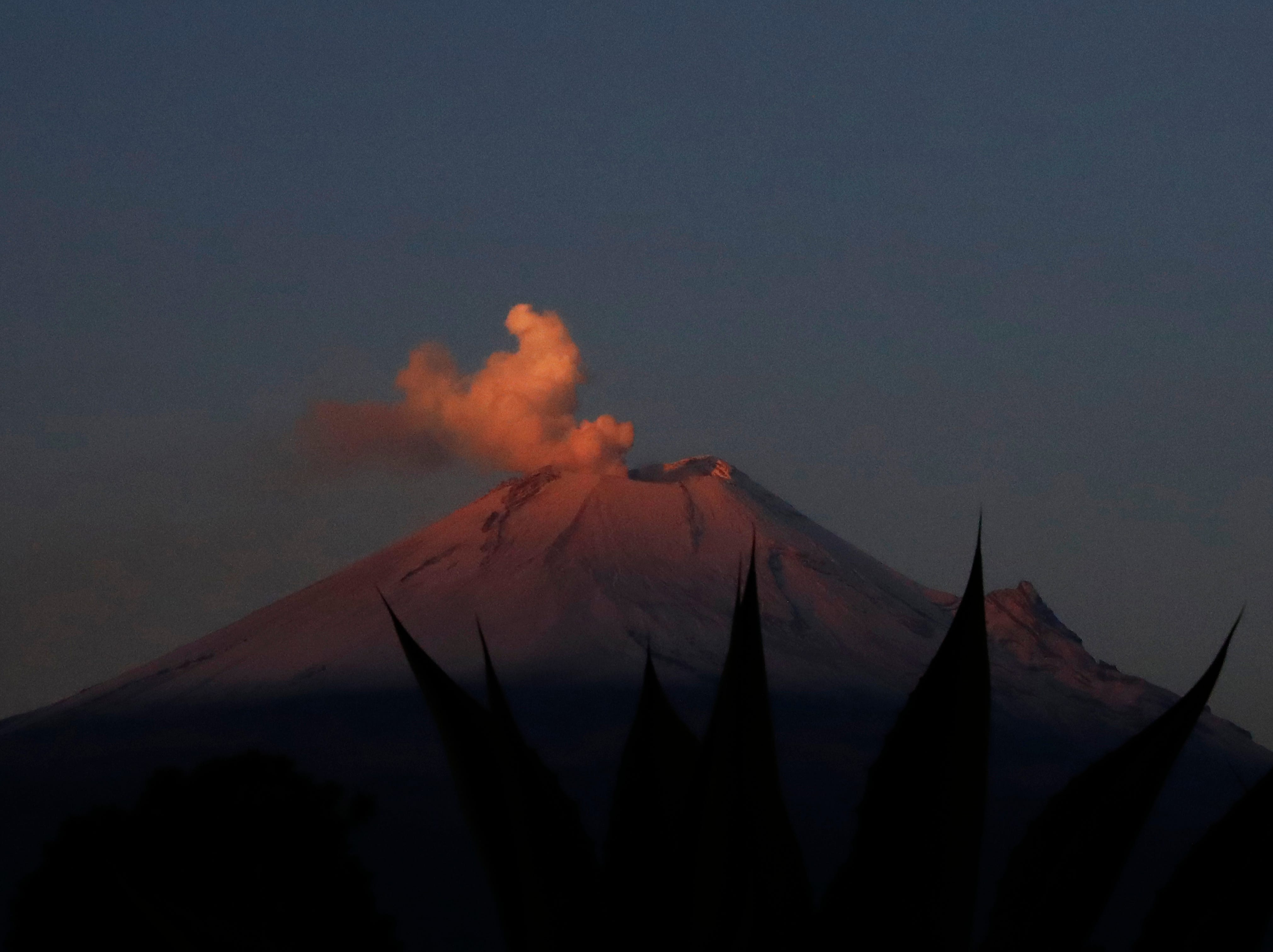 """In this Thursday, May 2, 2019 photo, the Popocatepetl volcano releases a plume of ash as seen from the flanks of the Iztacchuatl volcano, near Santiago Xalitzintla, Mexico. Veronica Agustin says the community has gotten used to living with Don Goyo, a nickname for Popocatepetl. When Don Goyo gets angry, the ground vibrates, doors and windows shake -- she compares the sound to that of beans cooking in boiling water. """"The scare passes,"""" said Agustin."""