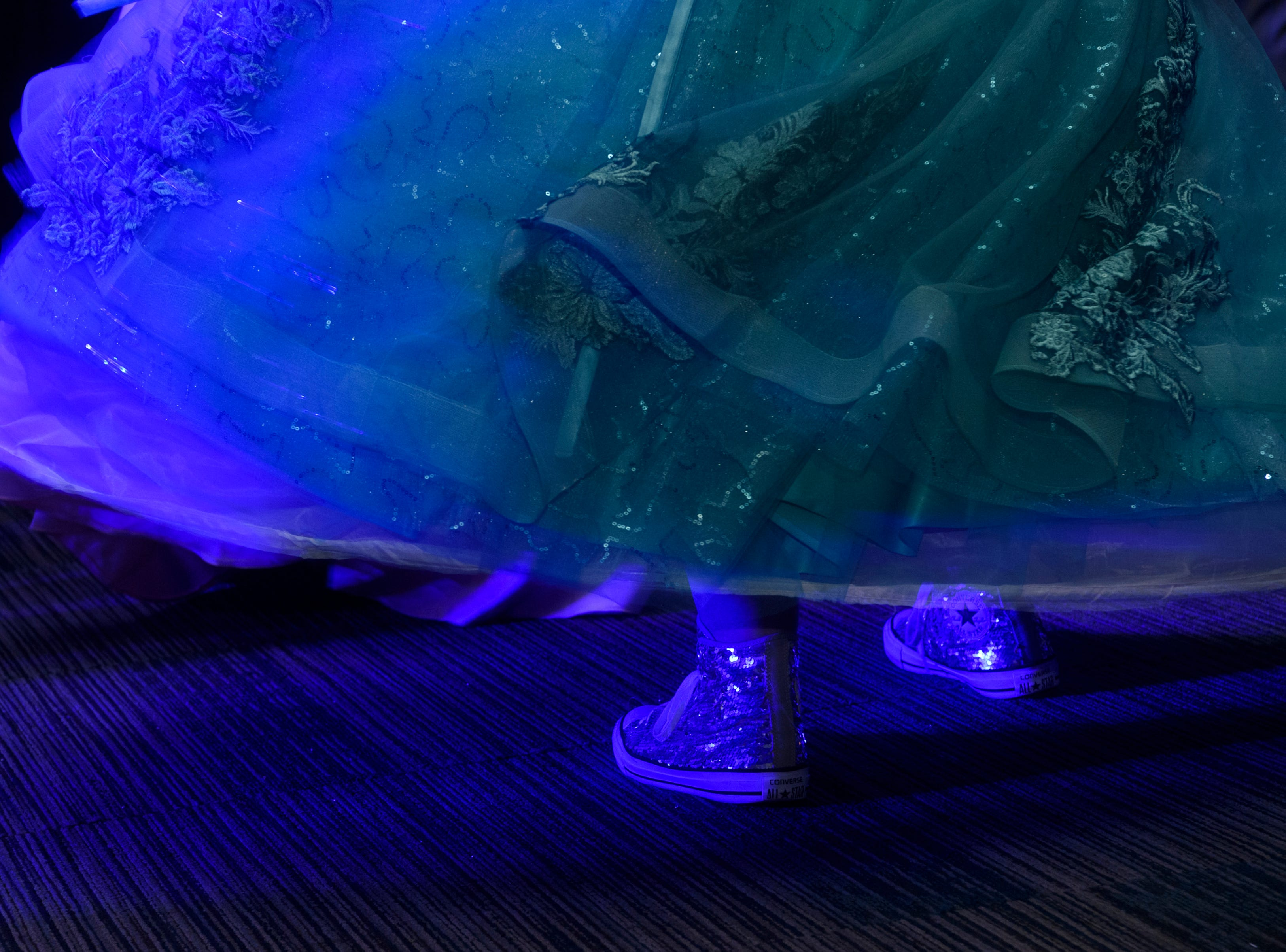 Mt. Vernon junior Alexis Adamaitis, left, dons glittery Converse Chuck Taylor shoes as she dances during prom held inside the University of Southern Indiana's Carter Hall in Evansville, Ind., Saturday, May 4, 2019.