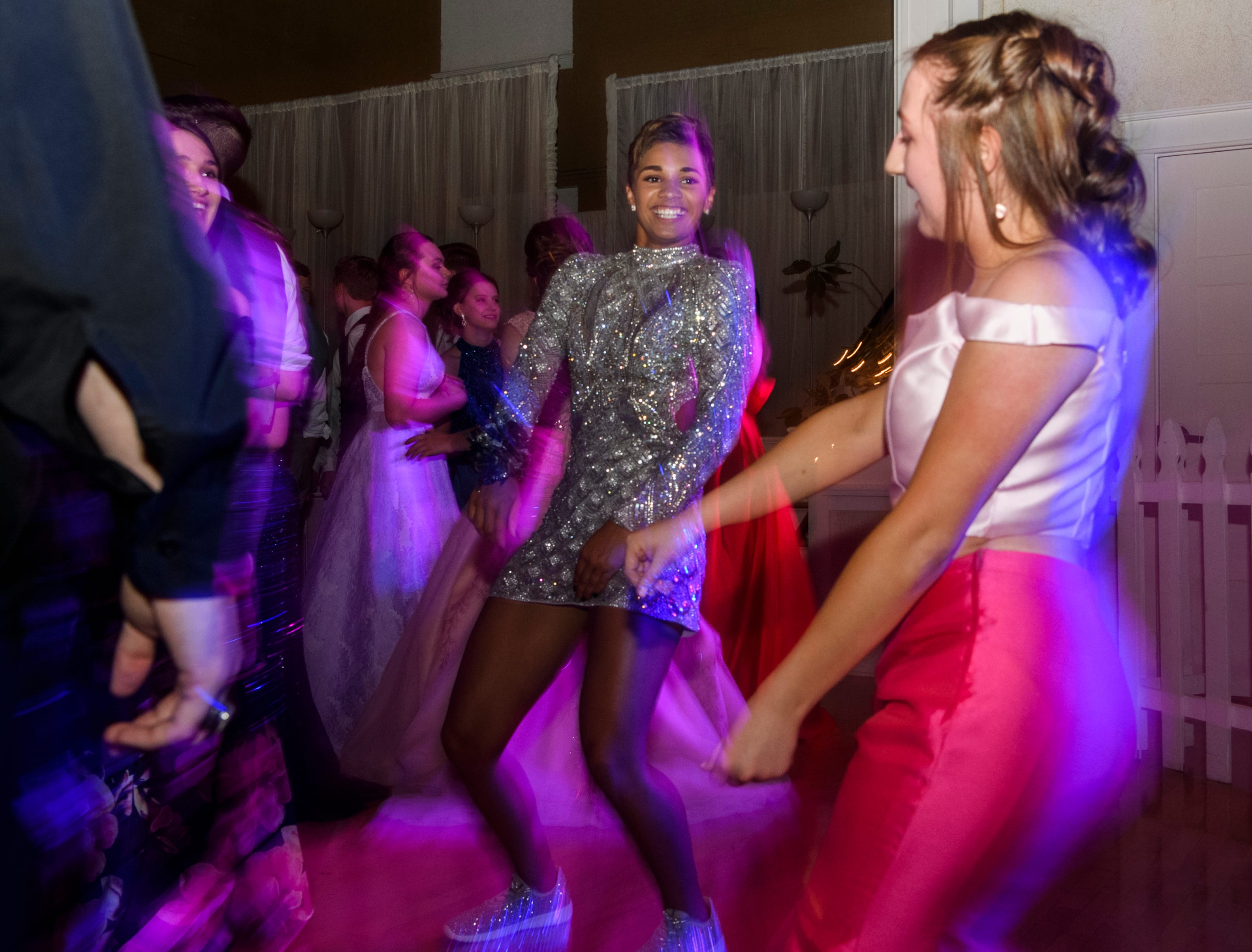 Madison Cates, center, and Abbey Myers, right, dance together during North Posey's prom held at the Ribeyre Center in New Harmony, Ind., Saturday, May 4, 2019.