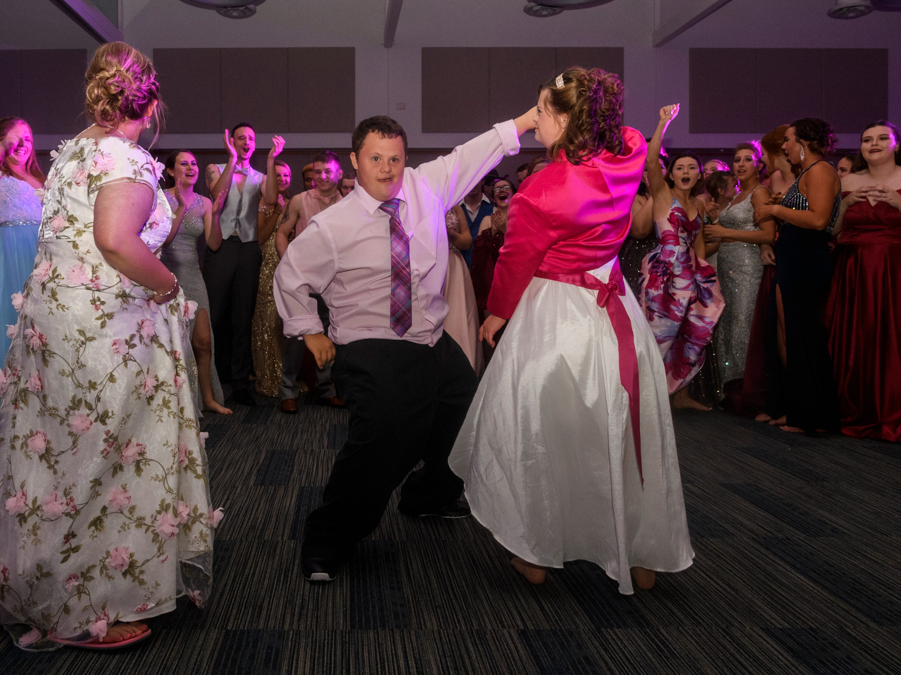 Kylee Ricketts, left to right, Ethan Sutton and Rebekah Granderson dance together during Mt. Vernon's prom held inside the University of Southern Indiana's Carter Hall in Evansville, Ind., Saturday, May 4, 2019.