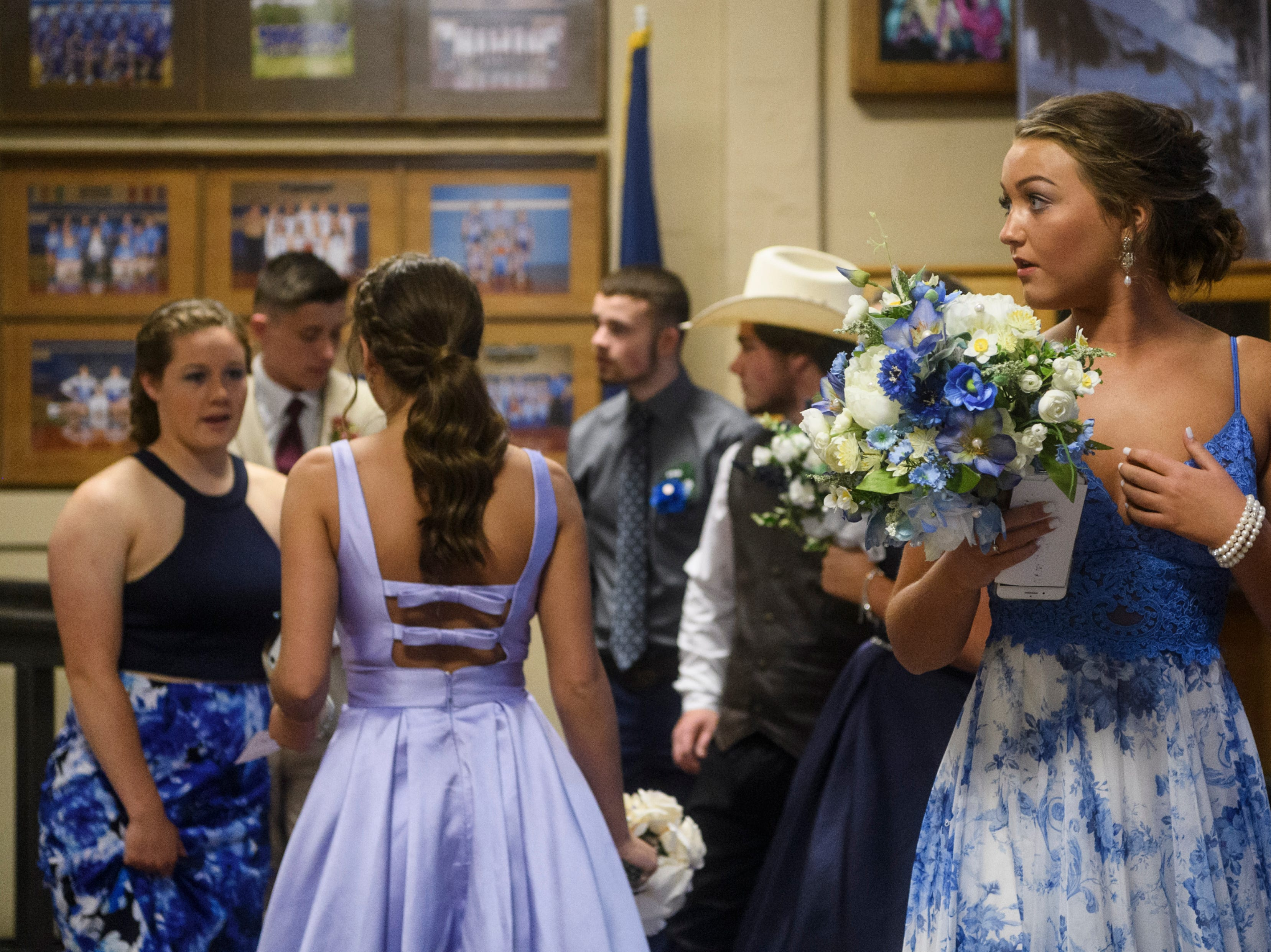 """Students mingle and wait patiently for the start of the """"grand march,"""" a tradition where they parade in front of family and friends before the start of North Posey's prom held at the Ribeyre Center in New Harmony, Ind., Saturday, May 4, 2019."""