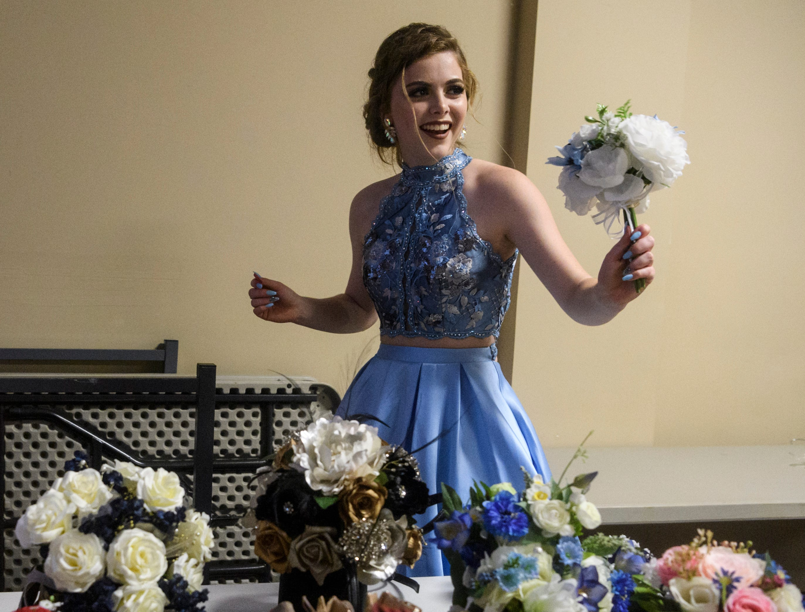 North Posey student Haylee Gengelbach puts her bouquet with her shoes and purse before going out on the dance floor during her prom held at the Ribeyre Center in New Harmony, Ind., Saturday, May 4, 2019.