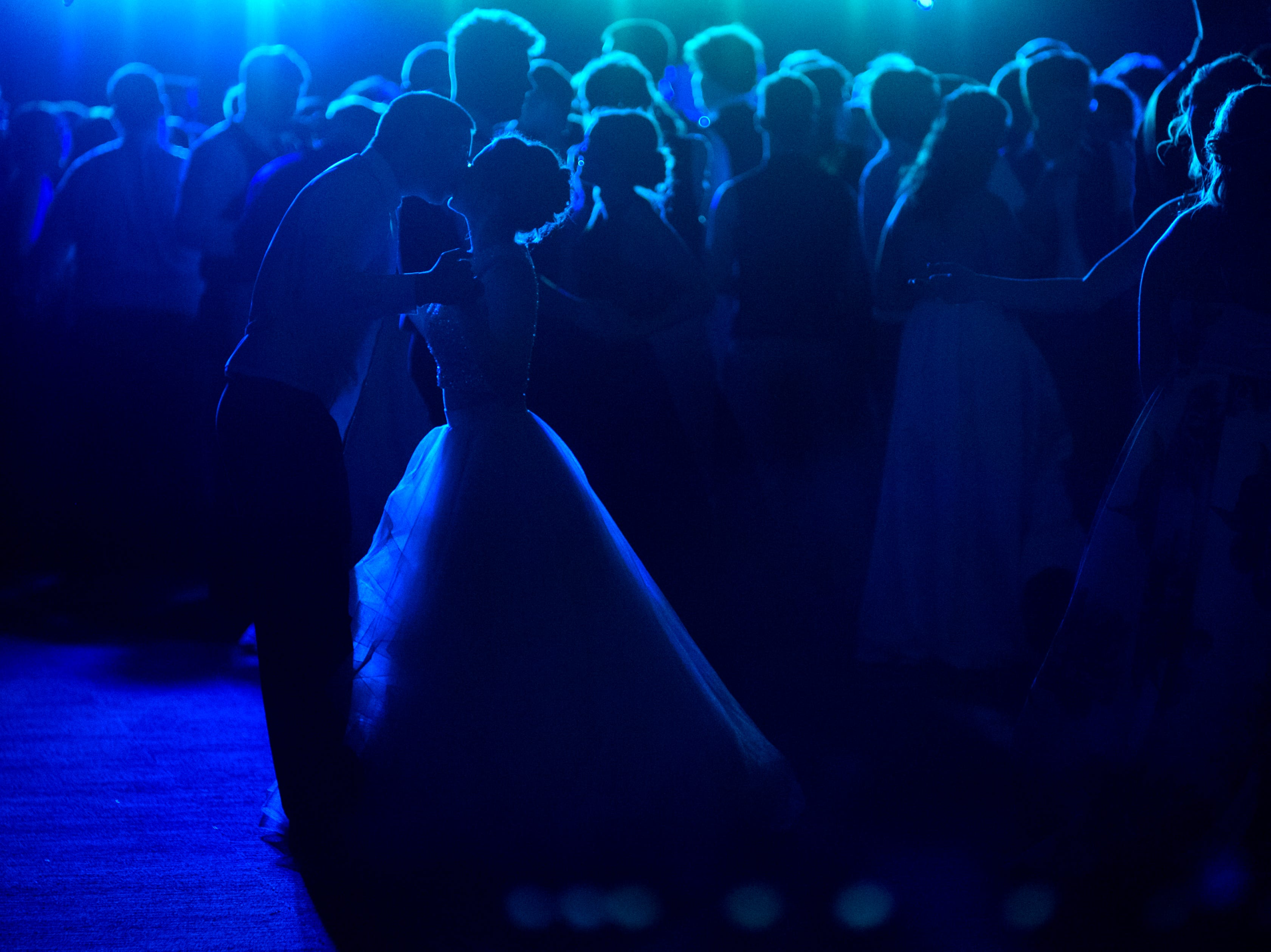 Johnathon Chaffin, left, leans in for a kiss from his prom date Alexis Macon, right, as they dance along with other Mt. Vernon High School students at University of Southern Indiana's Carter Hall in Evansville, Ind., Saturday, May 4, 2019.
